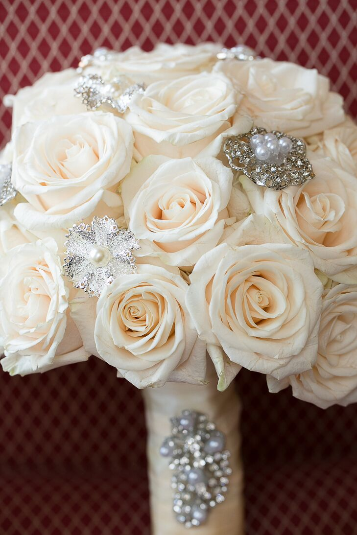 Vashti carried a bouquet of ivory roses with silver imitation roses embellished with pearls. The matching ivory bouquet wrap was also embellished.