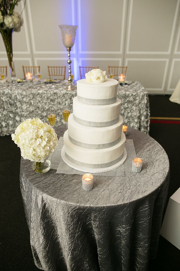 "Aaron's uncle made the four tier wedding cake, which was decorated with silver ribbon and topped with white lisianthuses. The cake was flavored ""blue velvet"" to match with the color scheme of the wedding."
