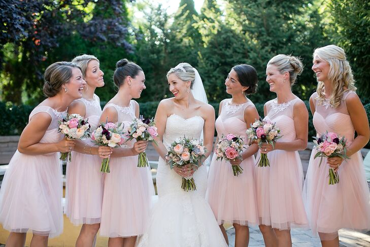 Mary's bridesmaids wore pink knee-length dresses by BHLDN with crystal embellished illusion necklines.