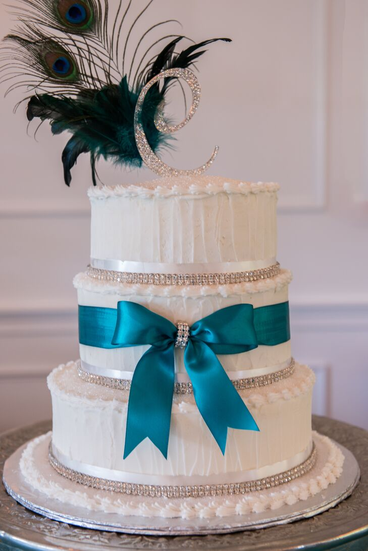 white wedding cake with turquoise ribbon and peacock