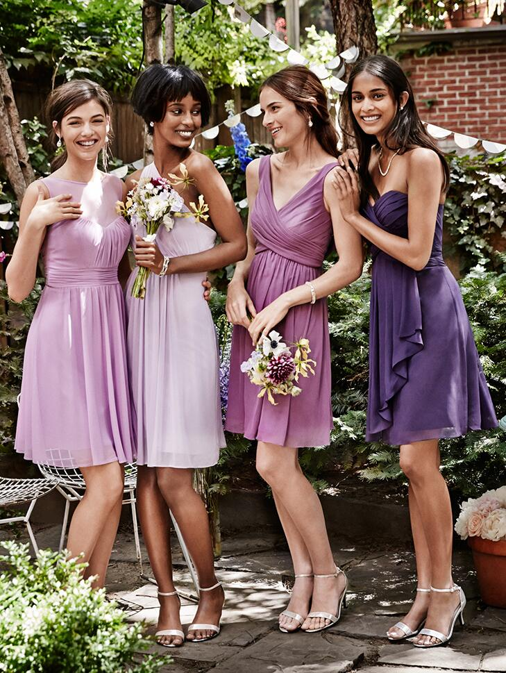 Women in four different purple bridesmaid dresses