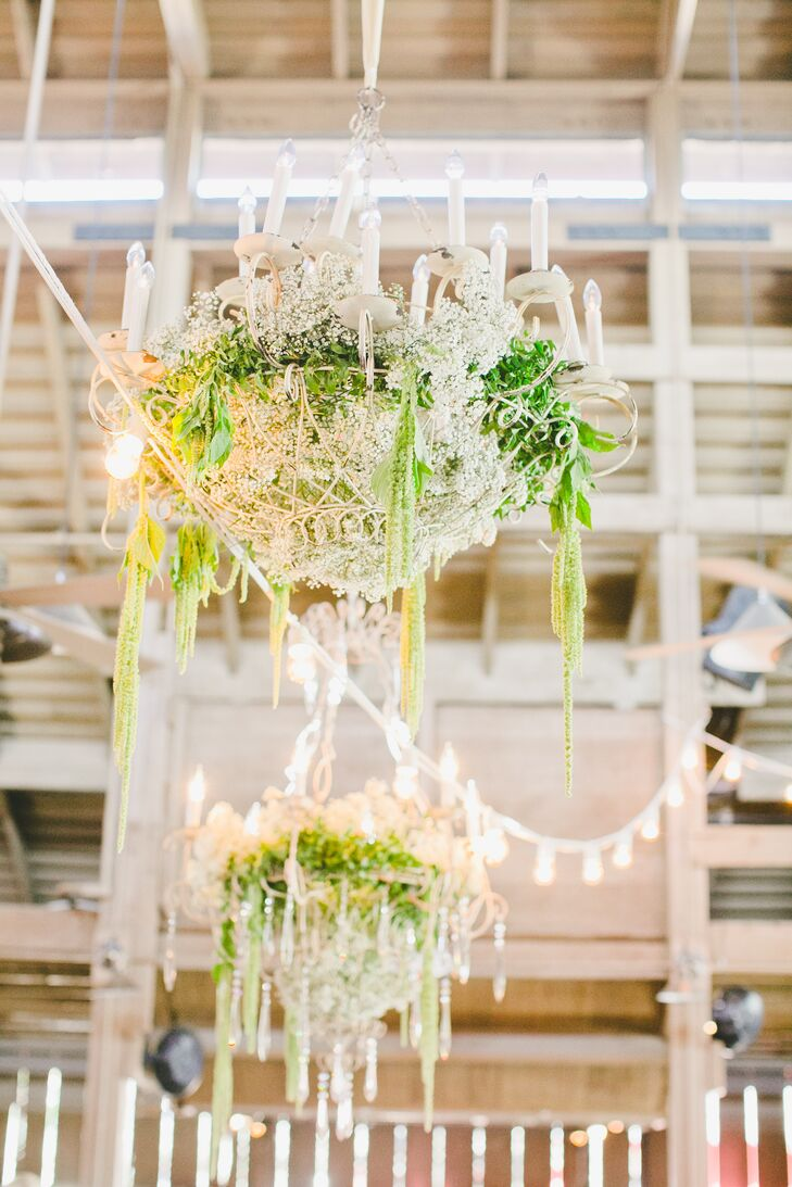 White Chandeliers Draped With Greenery
