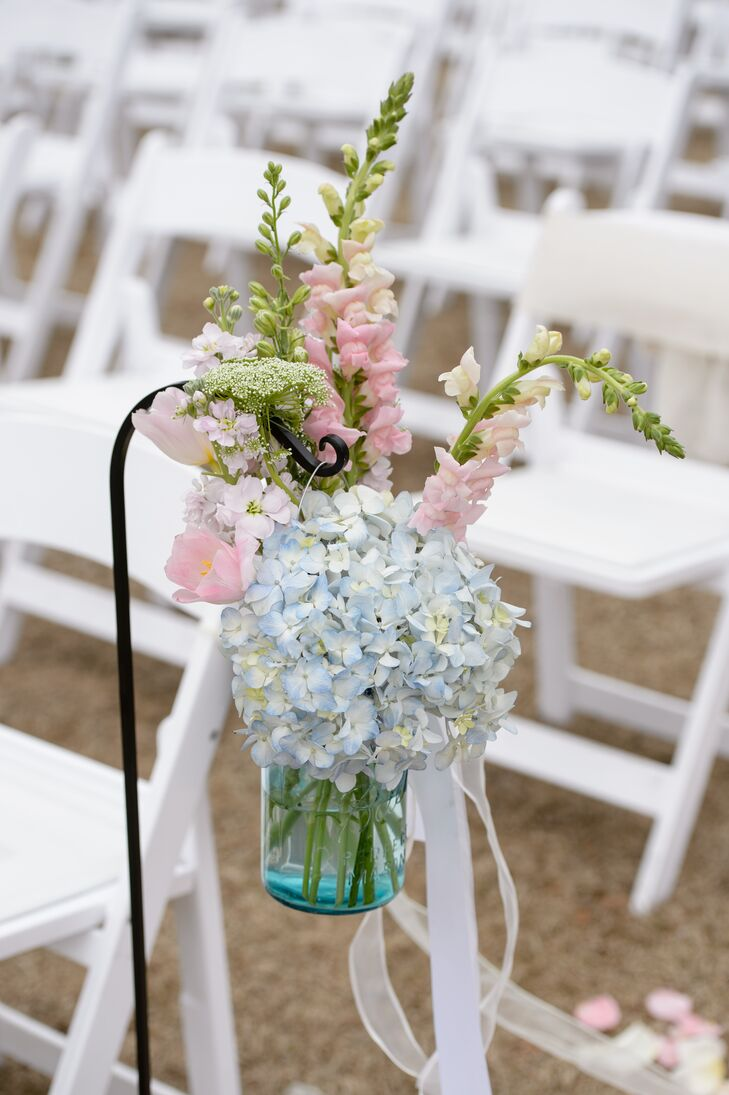 The King's Garden lined Mary Caroline and Forrest's outdoor wedding with a natural touch. Hanging arrangements of blue hydrangeas, pink delphiniums and pink tulips accented the front of their aisle as pink and white flower petals lined the floor.