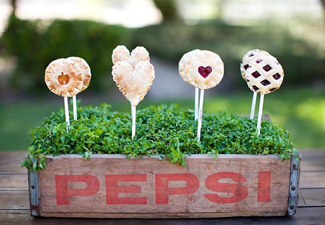 Pie pop wedding desserts in a rustic, vintage Pepsi crate.