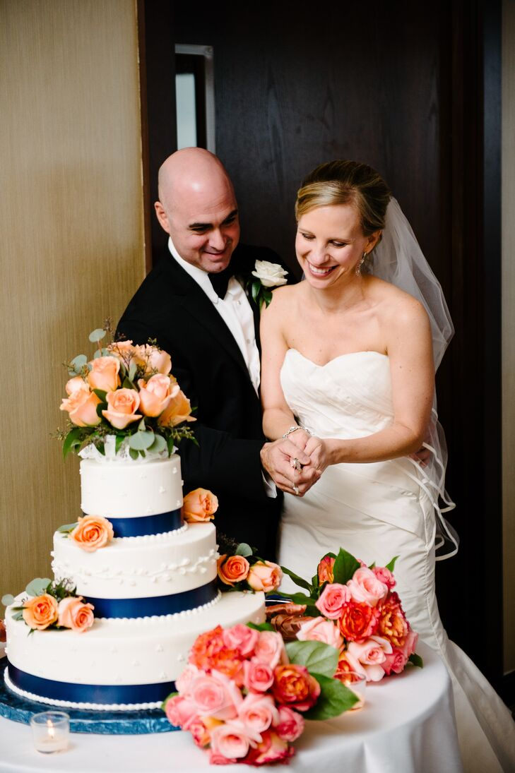 The couple's traditional wedding cake was given a cheerful touch with bunches of fresh coral roses dotting each tier.