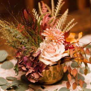Fall foliage and flower centerpiece in gold vase
