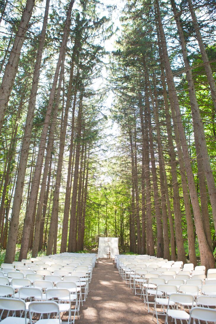 "The ceremony took place in an outdoor setting at Stony Creek Metropark in Shelby Charter Township, MI. ""The tall white pine trees that build a cathedral in the middle of the woods with shafts of light beaming through the trees was perfect for our ceremony,"" Adrienne shared."