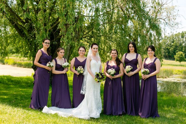 Yelena's bridesmaids wore floor-length, dark purple dresses with white bouquets matching the plum and white color palette.