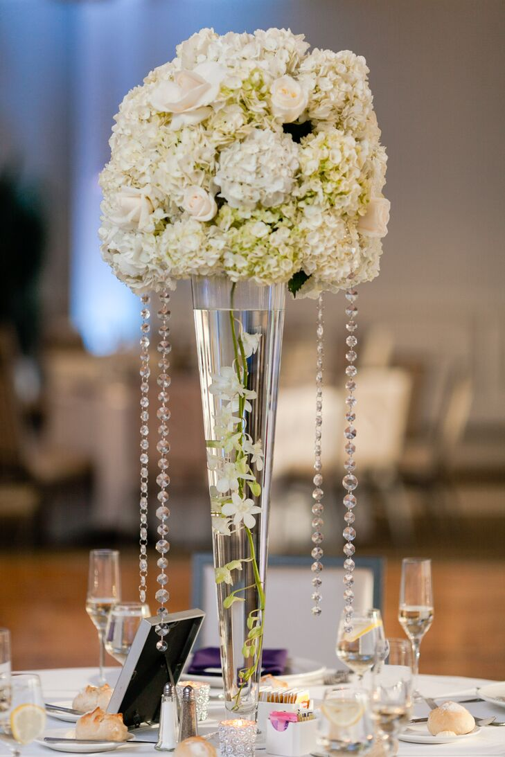 Following the simple and elegant style of the wedding, white rose and hydrangeas bouquets in tall glasses acted as centerpieces for the reception tables.
