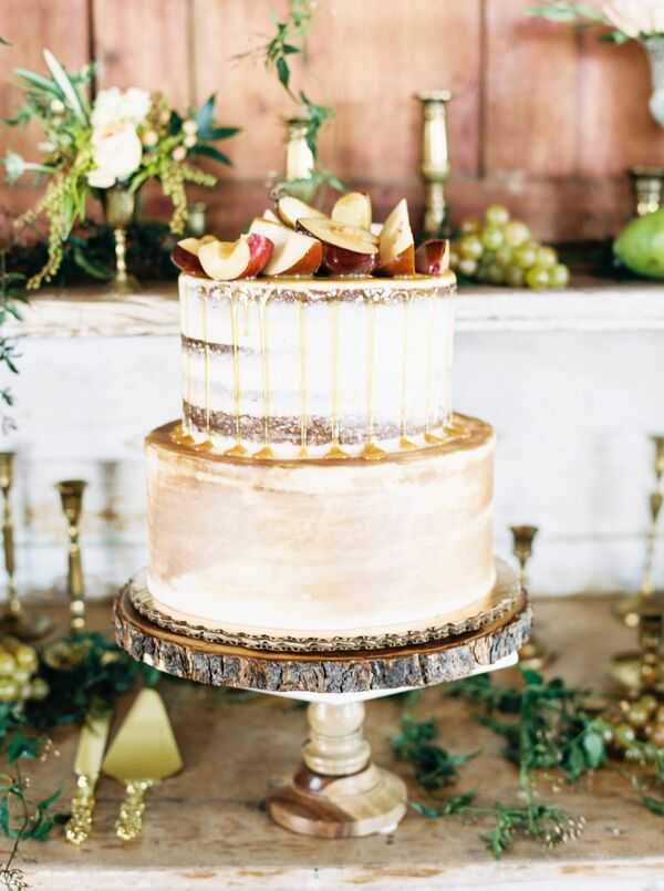 naked cake on tree slice stand topped with apples