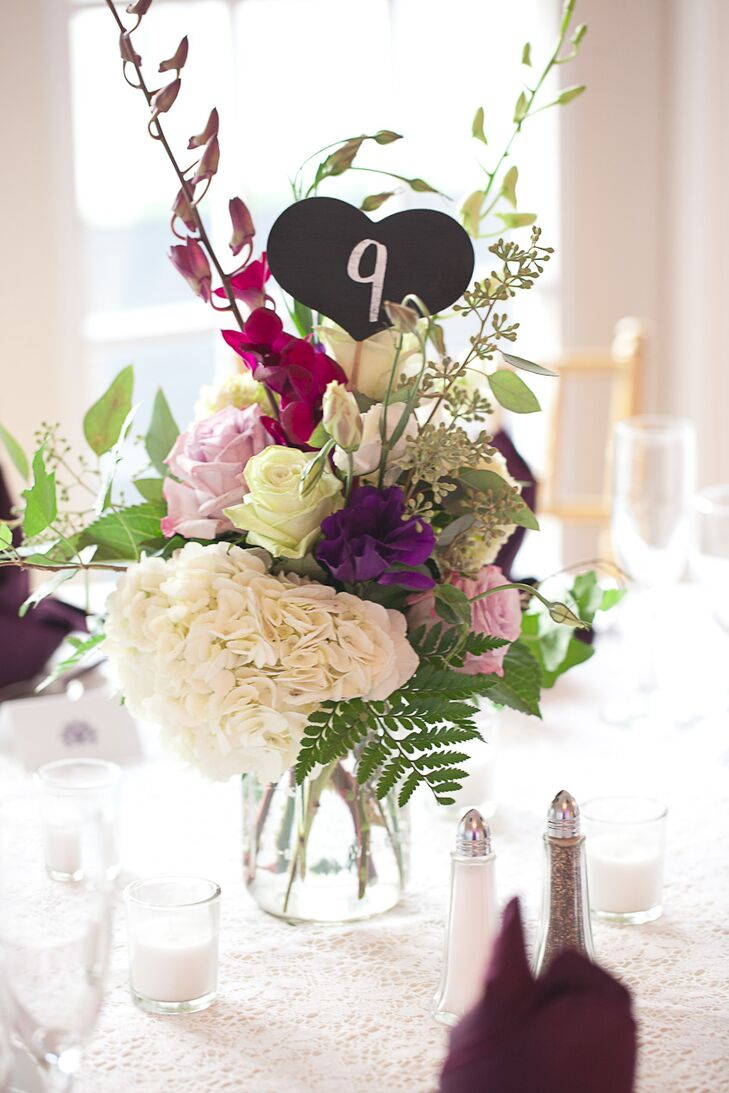 The reception tabled held ornate plum, pink, and ivory arrangements of hydrangeas, roses, chrysanthemums, and dendrobium orchids for a variety of bold shapes and textures. Sophia also ordered small chalkboard heart table numbers from Etsy.