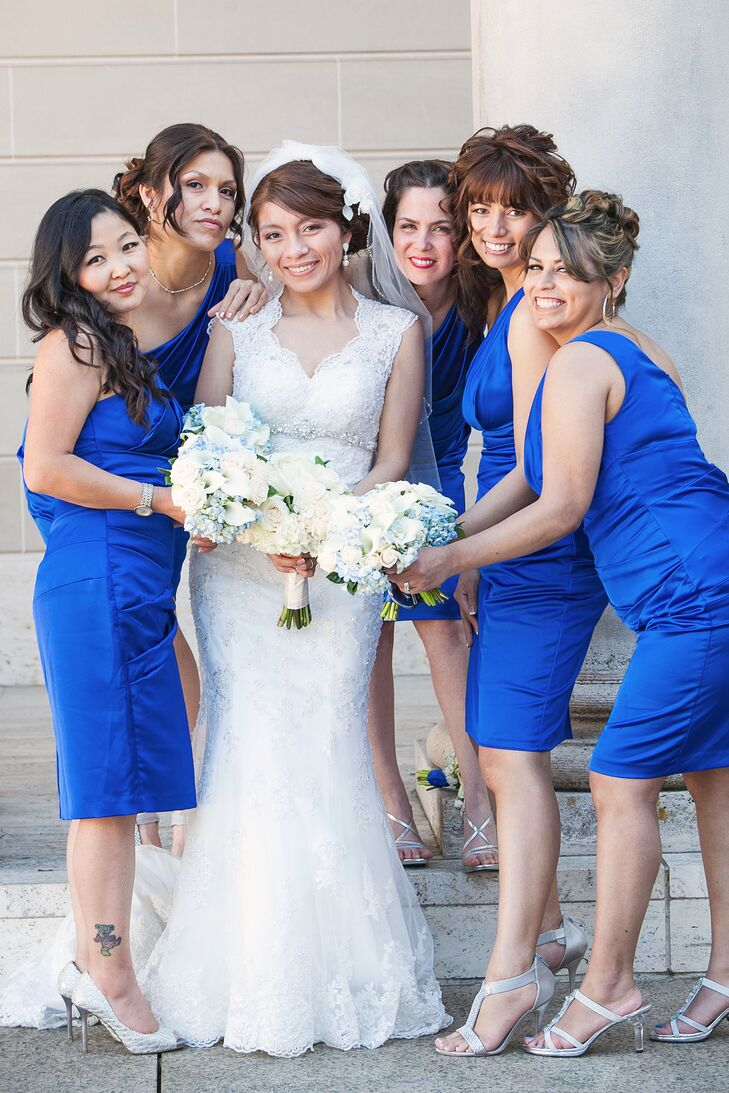 The bride posed with her bridesmaids, who wore one-shoulder satin dresses in royal blue.
