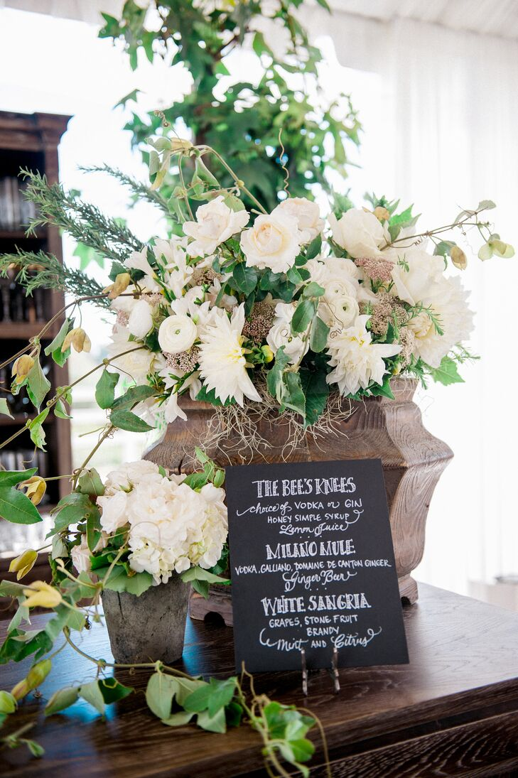 A black-and-white chalkboard sign displayed the speciality cocktail options, set up in front of a large overflowing arrangement filled with ivory blooms.