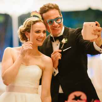 Bride and groom with photo booth props taking a selfie