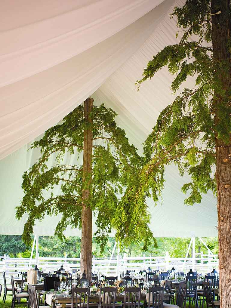 Faux tree covers for tent poles at an outdoor wedding