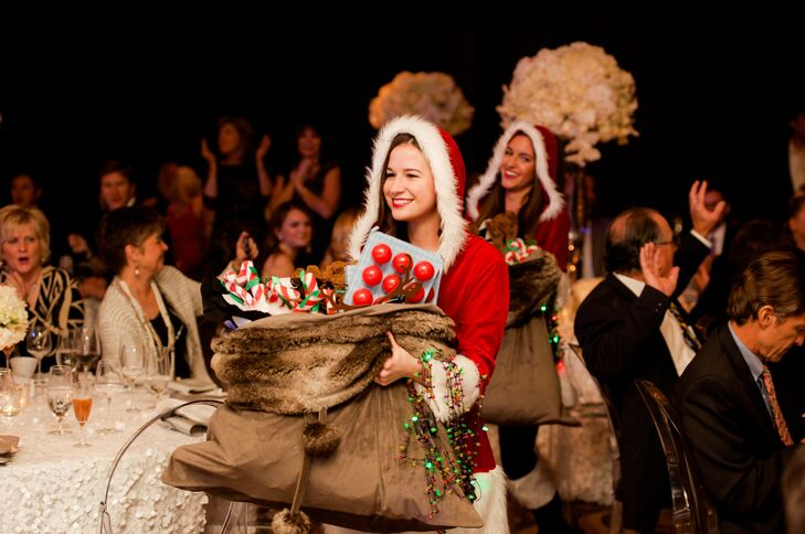 "As Dance Street Band played ""All I Want For Christmas Is You,"" Santa's helpers popped into the reception with bags of Christmas-themed apparel for guests to wear before a grand entrance by Santa Claus."