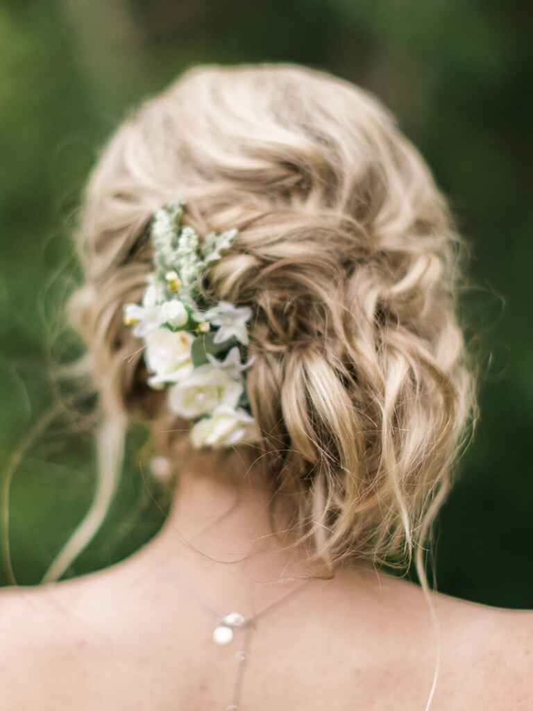 Messy bridesmaid wedding updo with flowers