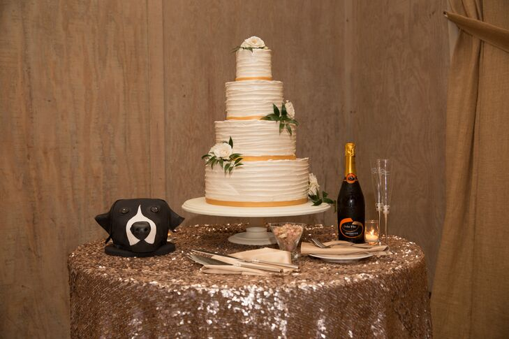 The four-tier ivory wedding cake was  decorated with gold at the bottom of each layer, and the entire piece was positioned on top of a simple white stand. The cake table was dressed in a gold glamorous tablecloth, which also displayed the groom's cake resembling a dog and a bottle of champagne.