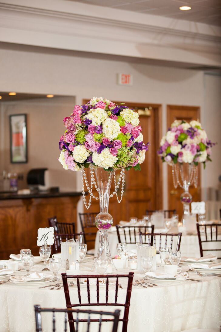 Tall glass vases held ivory and purple hydrangea, rose and iris flower arrangements. The centerpieces also had elegant strings of crystals to drape from the flowers for extra sparkle.