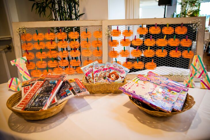 The escort table had orange cards dangling from wooden frames with author names identifying which table guests were seated at. Baskets filled with children activities were placed in front of the escort cards.