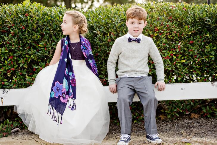 Flower girl and ring bearer in purple and white outfits