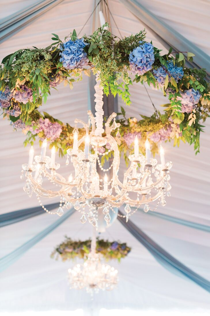 Greenery and blue hydrangea wreaths were paired with crystal chandeliers to create a floral focal point at the couple's tented reception.