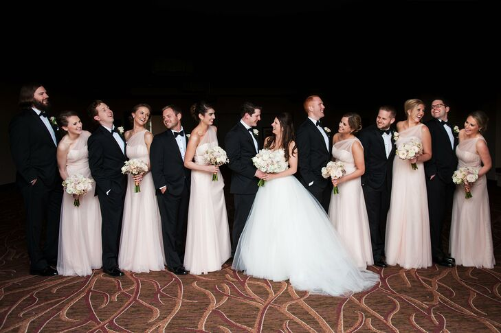 The bridesmaids wore one-shouldered, floor-length blush Watters dresses. The groomsmen wore classic black tuxedos with suspenders and black bow ties. Kathleen and Alan loved how formal the wedding party looked and how their attire matched the black, white and blush palette.