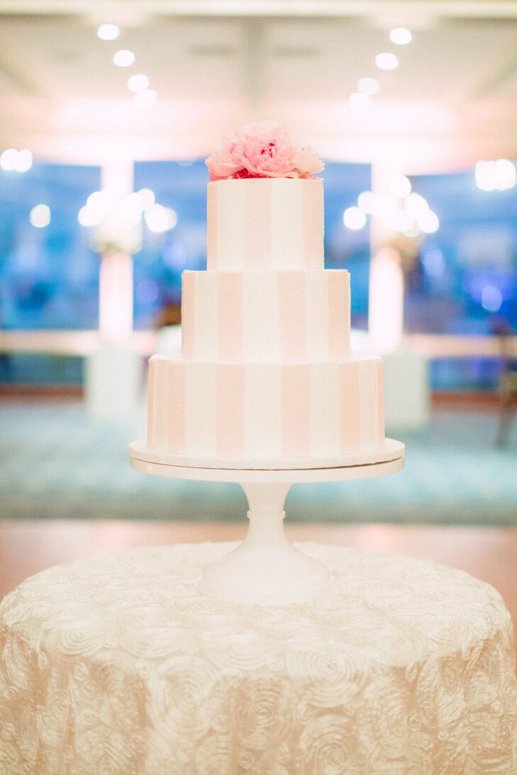 Light pink vertical stripes decorated the three-tier white cake.