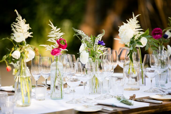 Reception tables were decorated with white hemstitch table runners and floral arrangements of ranunculus and astilbe in mixed vintage glass vessels created a lush, wildflower look.