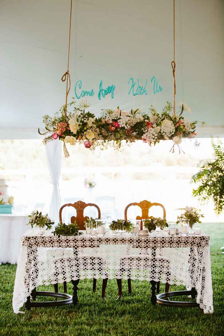 Couple's table with crochet tablecloth and hanging florals and sign