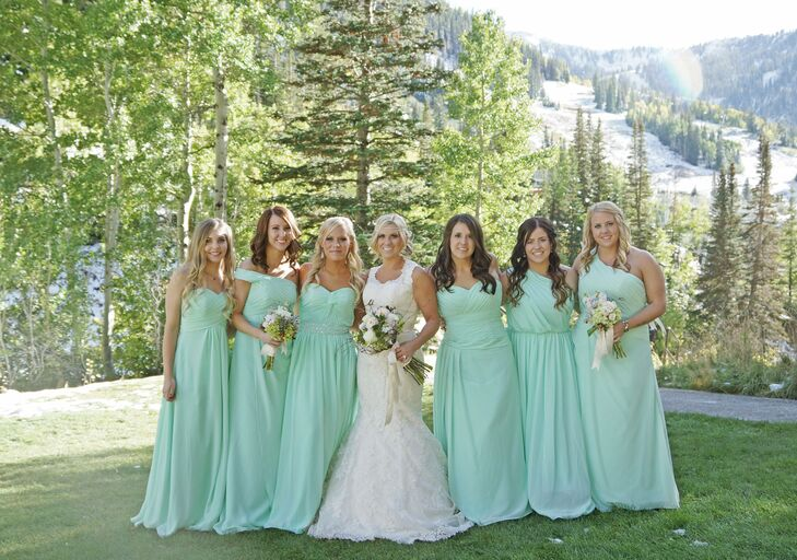 Miranda's bridesmaids' mint dresses added a delicate pop of color to the natural mountain setting. They chose different styles of a floor-length dress and carried white and green bouquets.