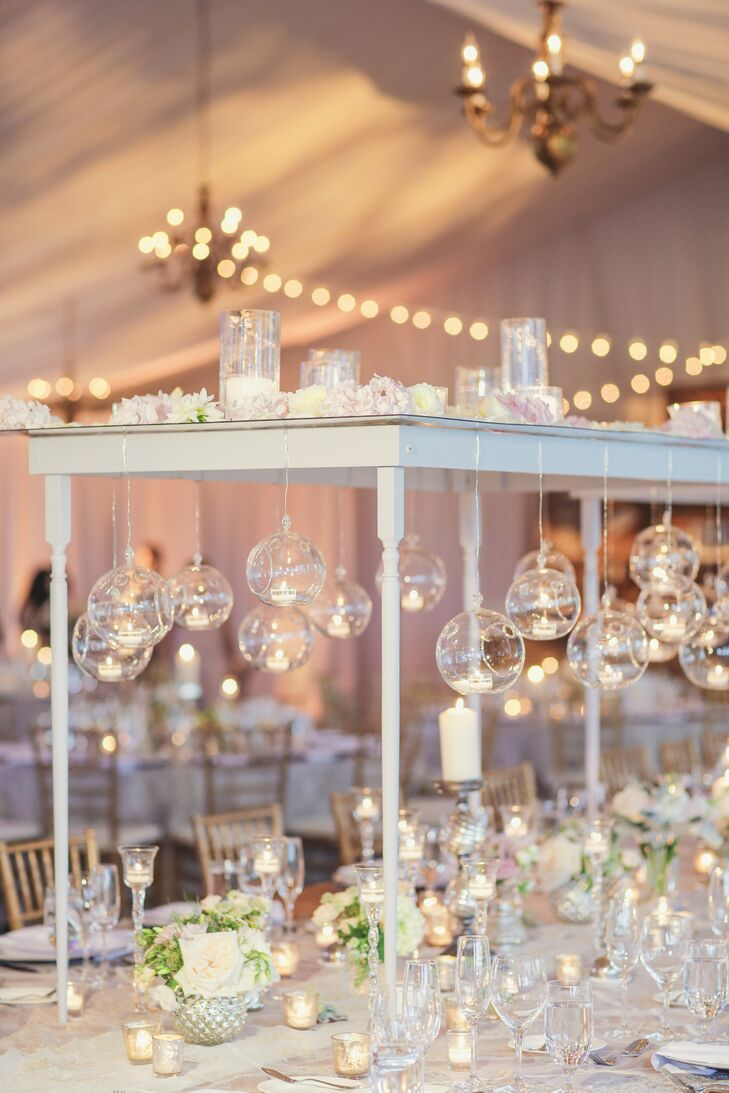 The head reception table featured an extravagant installation. A custom-built table-like structure stood in the center. Globes filled with candles hung from the underside and candles, and flowers were placed on top.