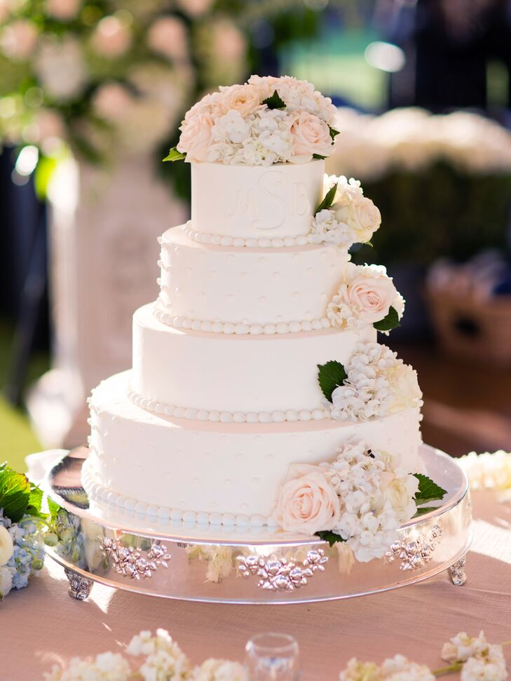 The four-tier white cake had fresh flowers on the top layer and cascading down the sides.