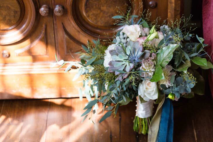 """Annie chose bouquets that were more wild, natural, and textured rather than tightly formed,"" the couple says. ""Bouquets made of cafe au lait dahlias, spray roses, succulents, blue eryngium, white freesias, seeded lemon leaves, mums and seeded eucalyptus sprayed gold were wrapped with gold and dark teal ribbons to match the palette."""