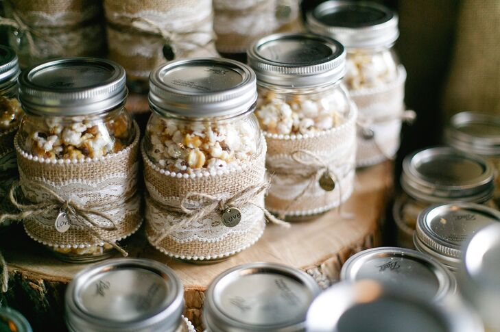 "Katharine and Marc's favors were DIY mason jars filled with homemade caramel popcorn. Katharine made the popcorn, while her mother helped decorate the mason jars in burlap and lace with a little ""love"" charm."