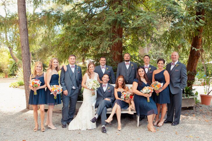 Sophie and Ryan posed in the middle of their wedding party dressed in navy blue and gray attire. The bridesmaids wore short navy dresses in their choice of style, while the groomsmen wore gray suits accented with a fun patterned bow tie.