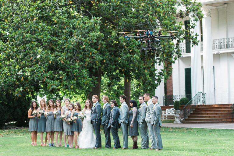 Bridal party smiling for pictures with the bride and groom outside while a drone hovers above them