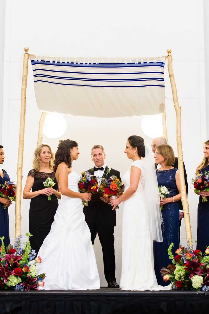 "Rather than having a flower girl and a ring bearer, Andrea and Nicole had four chuppah bearers. ""In keeping with the theme of unity, one person from the maternal and paternal sides of each of our families carried the chuppah,"" Andrea says. The chuppah was made using Andrea's father's tallith."