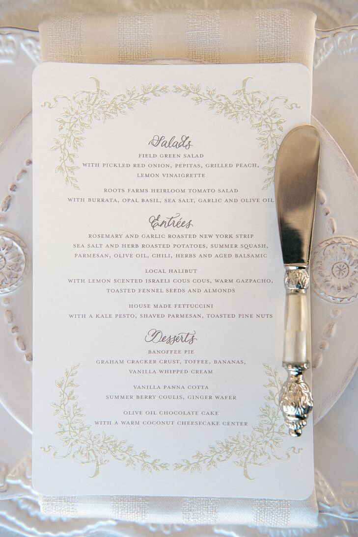 White stationery with gold designs bordering around the text let guests know of what to expect for the upcoming meal. White plates set under the menus added to the overall elegant setting.