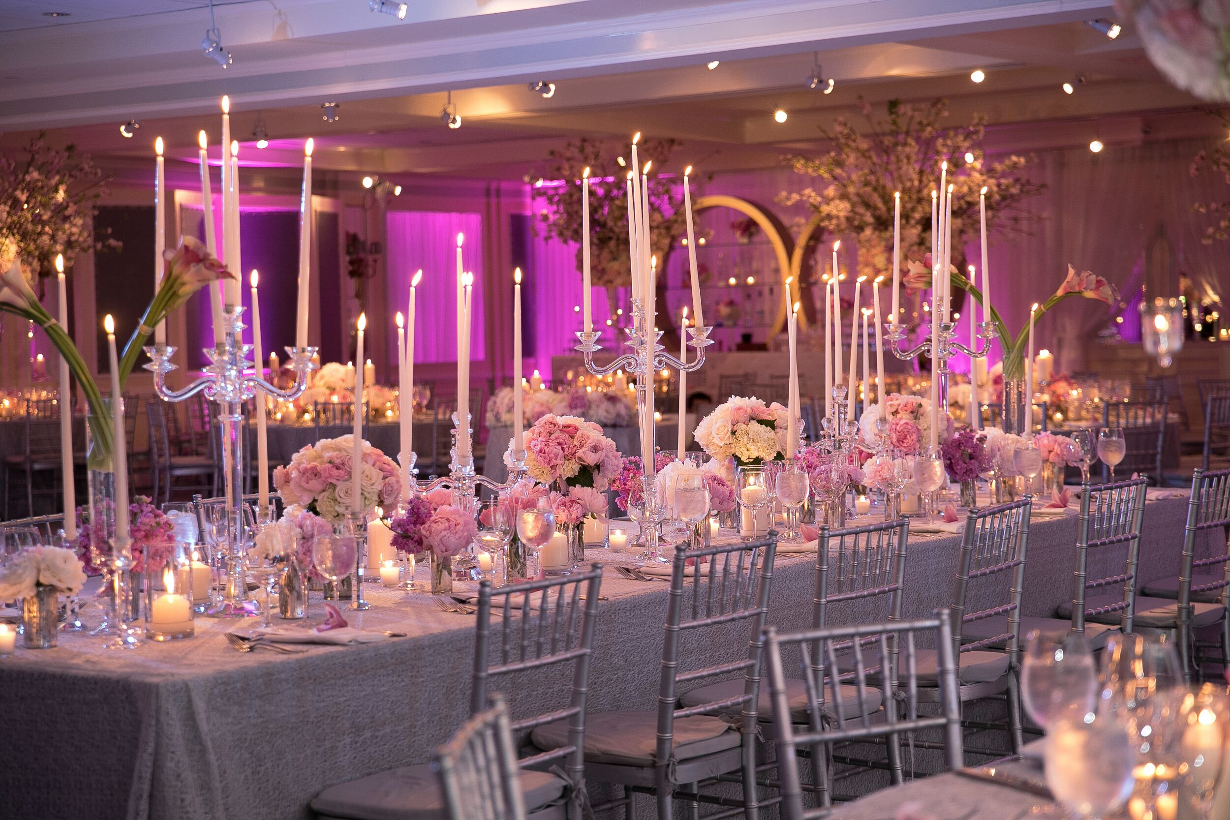 Long Reception Table with Pink Centerpieces and Tall Candelabras