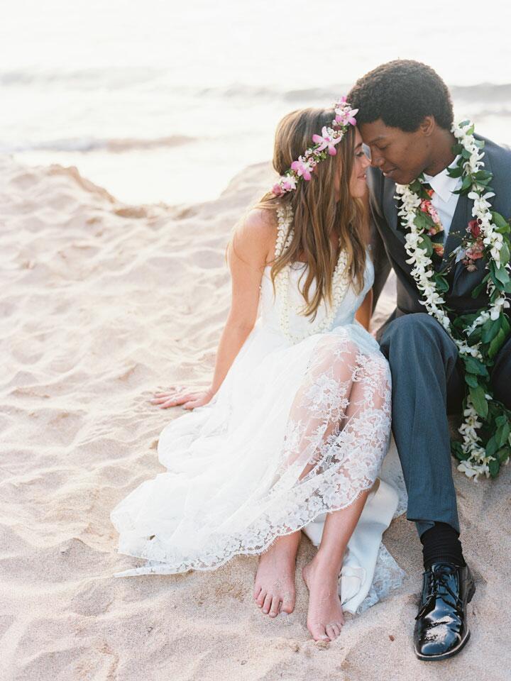 couple sitting on beach in Hawaii