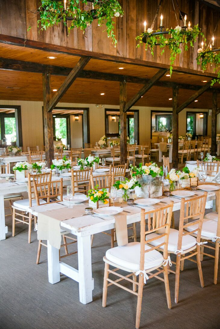 The plantation's carriage house, where dinner and dancing were held, was decorated with with whitewashed farm tables, burlap table runners, wooden chiavari chairs and beautiful yellow, white and green floral arrangements.
