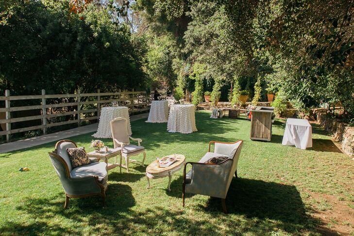 "After the couple said their ""I do's,"" they invited guests to mix, mingle and enjoy refreshing snacks and beverages on Calamigo's expansive lawn. Vintage furnishings brought an air of sophistication and elegance to the natural setting, while cocktail tables draped in textured linens and pretty pastel blooms played into the day's whimsical theme."