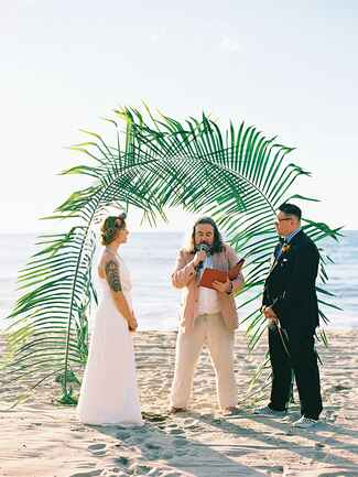 Beach wedding altar idea with large palm tree leaves