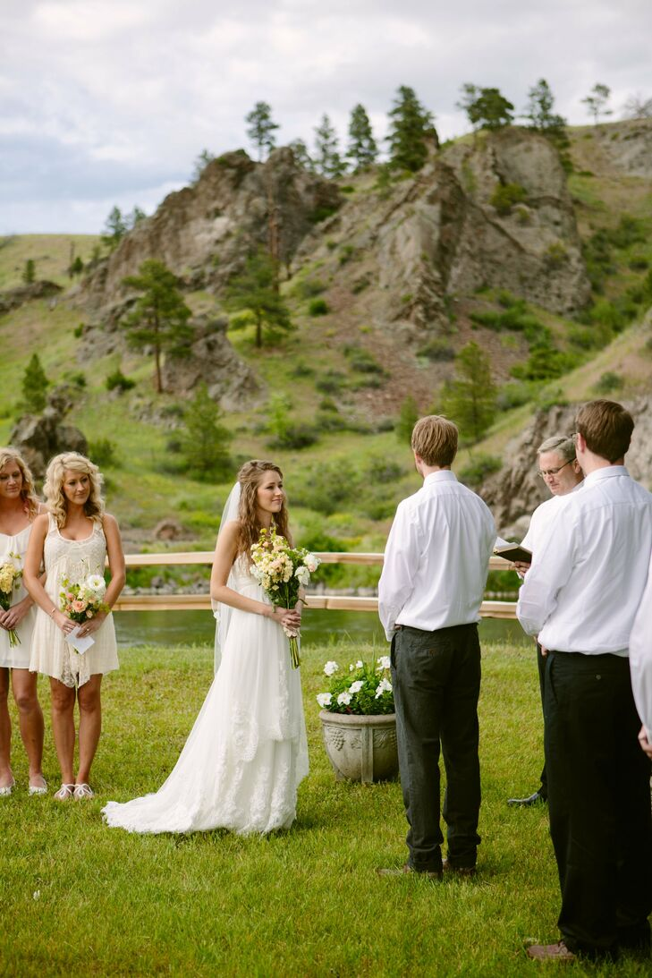 The bride and groom exchanged vows in a mountainous outdoor space bordered by a fence.