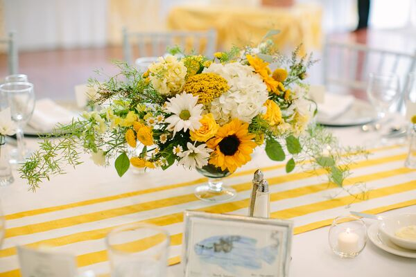 Stock flower bright centerpiece with sunflowers and daisies on striped table runner mightylinksfo