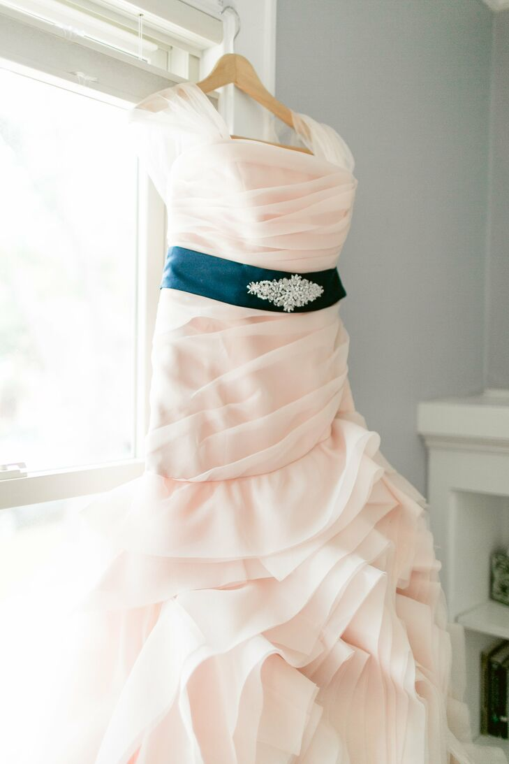 "Mary wasn't wasn't seeking a specific type of wedding gown but wanted more than a traditional white dress. She saw a strapless organza blush trumpet-style Vera Wang when it initially debuted, and it left an impression. After she tried it on, ""the color and feel were perfect,"" she says, adding that no other dress compared. She bought the matching blush veil and used a portion of the material to create small cap sleeves, then added a navy belt to match the bridesmaid dresses."