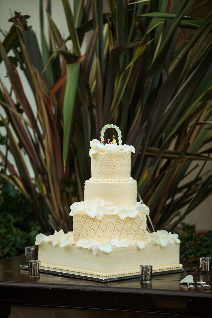 The four-tier ivory wedding cake had textured patterns on every tier, which had white rose petals scattered on the surface of each layer. The cake was topped with Lego versions of a bride and a groom.