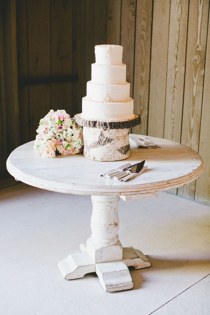 The four-tier wedding cake had delicate beading on top and around the layers of the dessert, perched up on a stand made of tree bark. A white-painted wooden table displayed the entire cake at large, with an elegant silver serving set on the side.