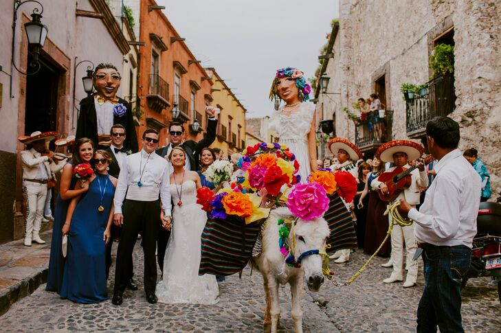 After exchanging vows in a traditional Catholic ceremony at Templo de la Inmaculada Concepcion, Marian and Dillion led their families and friends through the streets of San Miguel de Allende, Mexico, in a customary callejoneada. A donkey adorned with colorful paper flowers led the procession, with a mariachi band and puppets made in the likeness of the couple adding a festive flair to the parade.